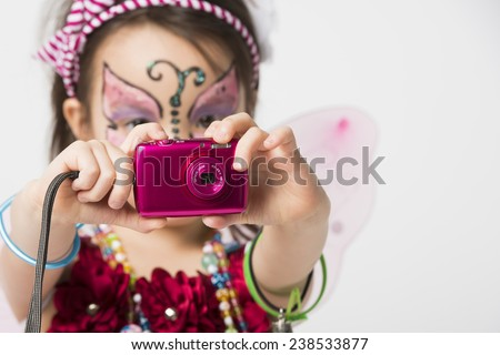 Little girl with face painting holding  a snapshot camera