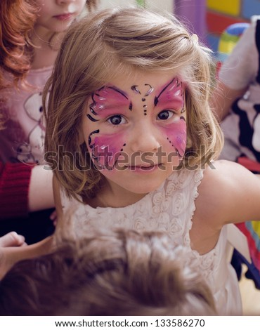 little girl with faceart on birthday party - stock photo