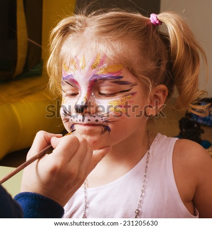 little girl with faceart on birthday party in process - stock photo
