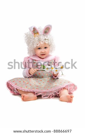 Little girl with flowers in hand wearing a dress. Isolated