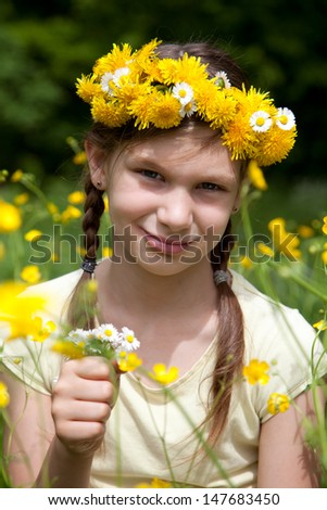Little girl with flowers in her hair on a meadow in nature