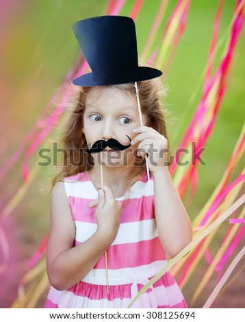 little girl with funny paper mustache and hat - stock photo