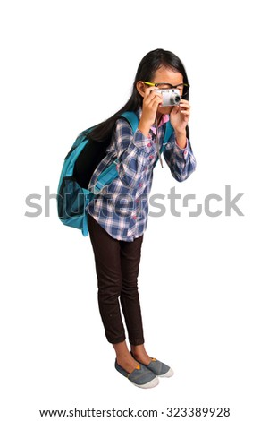 Little girl with glasses and backpack standing and taking photo with her camera isolated on white