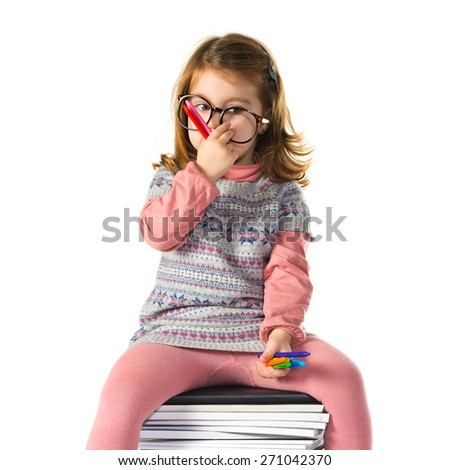 Little girl with glasses sitting on books - stock photo