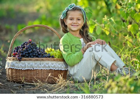 Little girl with grapes outdoors
