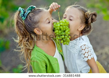 Little girl with grapes outdoors - stock photo