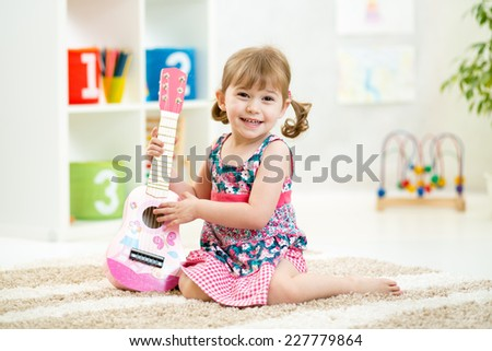 little girl with guitar toy gift siiting on floor - stock photo