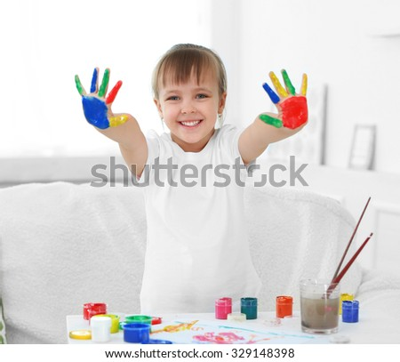 Little girl with hands in paint, on home interior background - stock photo