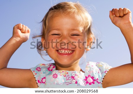 little girl with hands up in success position - stock photo