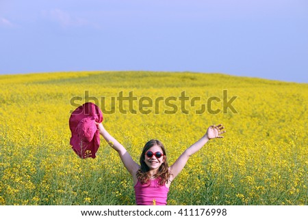 little girl with hands up on yellow flowers field summer season - stock photo