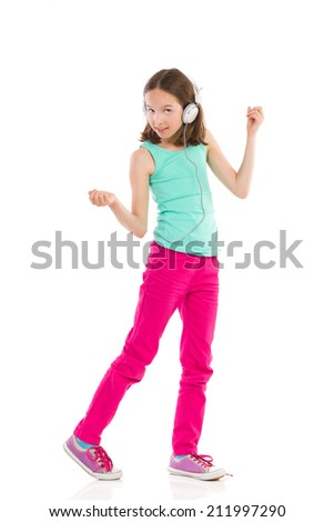 Little girl with headphones dancing and listening to the music. - stock photo