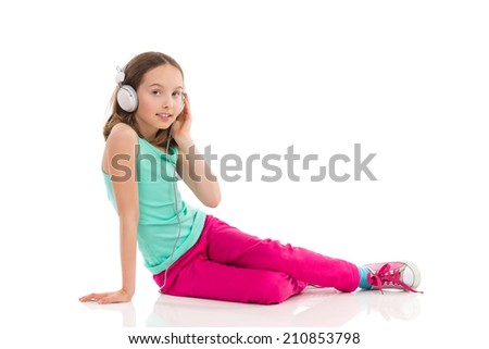 Little girl with headphones is sitting on the floor and listening to the music. Full length studio shot isolated on white. - stock photo