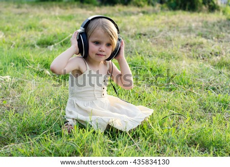 Little girl with headphones listening music. Girl with surprised face expression. - stock photo