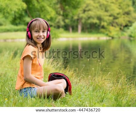 Little girl with headphones listening to music at lakeside. Child have rest near water in park. - stock photo