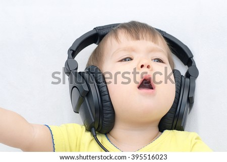 little girl with headphones singing song loudly