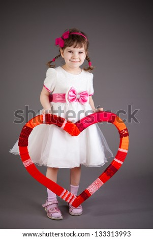 little girl with heart in a dress on a gray background