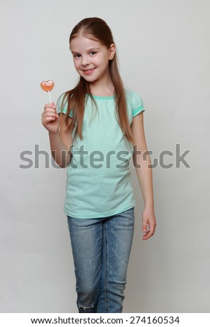 Little girl with heart symbol lollipop - stock photo