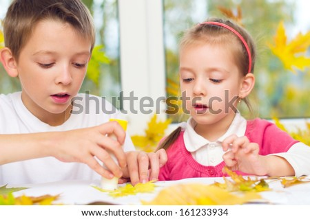 little girl with her brother applying a dry maple leaves using glue while doing arts and crafts - stock photo