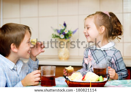 little girl with her brother sitting at the table drinking tea - stock photo