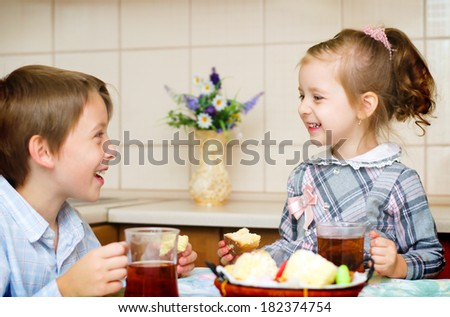 little girl with her brother sitting at the table drinking tea