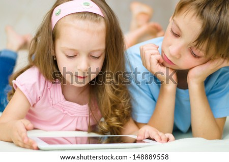 little girl with her brother using tablet computer - stock photo