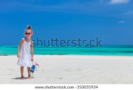 Little girl with her bunny toy enjoying tropical beach vacation - stock photo