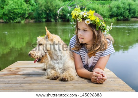 Little girl with her dog scottish terrier by the river in the summer - stock photo