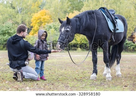Little girl with her father feeding the black horse apples. Gold autumn. Moscow. Russia. - stock photo