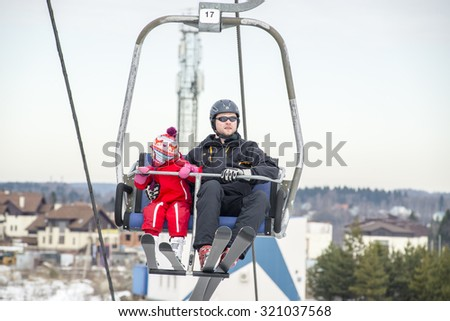 Little girl with her father skiing. On the lift.