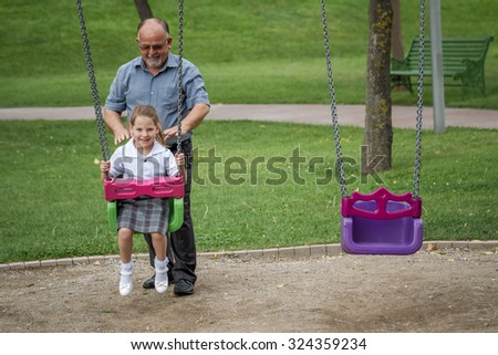 Little girl with her grandfather having fun on a swing in a green park - stock photo