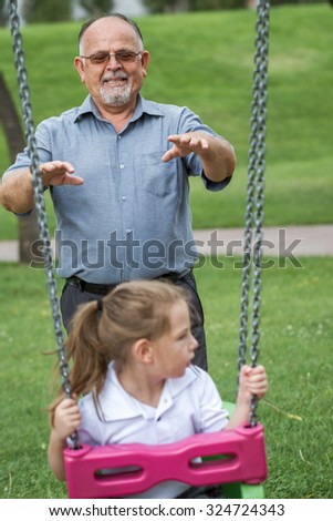 Little girl with her grandfather having fun on a swing in a green park