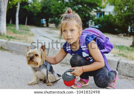 little girl with her little dog  on the walk in summer