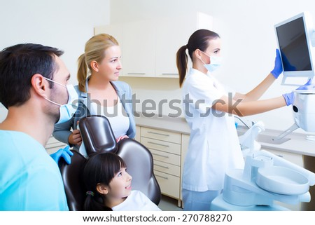 Little girl with her mother at the Dentist before treatment.  - stock photo
