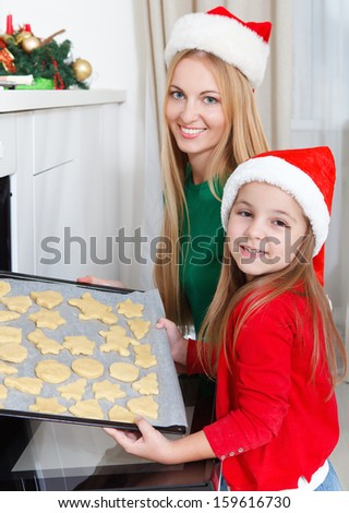 Little girl with her mother baking Christmas cookies at the kitchen - stock photo