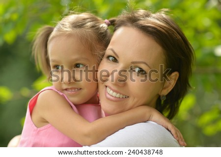 Little girl with her mother on a walk outdoors - stock photo
