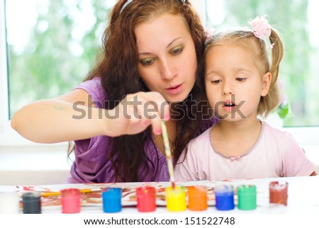 little girl with her mother painting indoors - stock photo