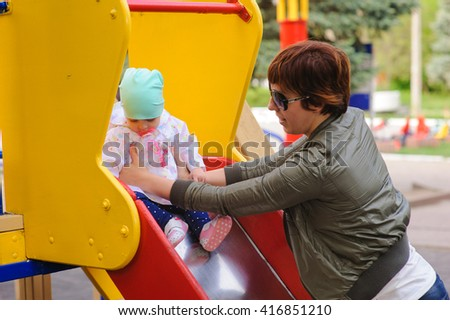 Little girl with her mother to the children's slides