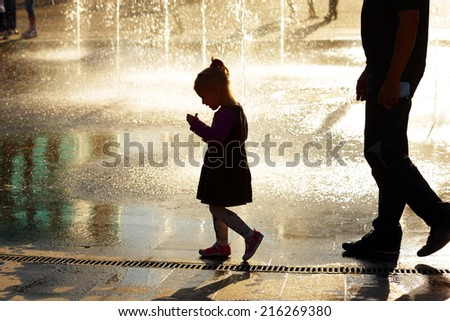 little girl with her mother under the spray of water from the fountain - stock photo