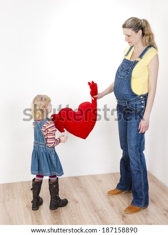little girl with her pregnant mother holding a heart - stock photo