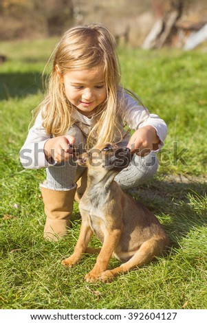 Little girl with her puppy dog , outdoor portrait, early springtime.