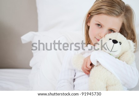 Little girl with her teddy sitting on the bed - stock photo
