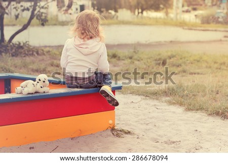 Little girl with her toy dog sitting in the sand box at child playground - stock photo