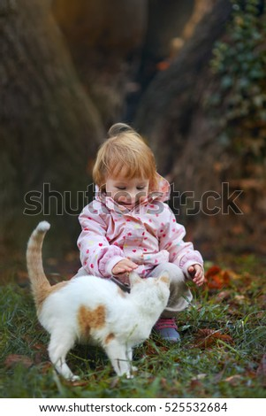 Little girl with homeless cat in autumn park