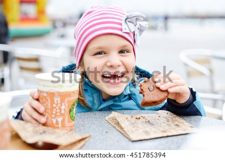 little girl with hot milk and cookie on the street - stock photo