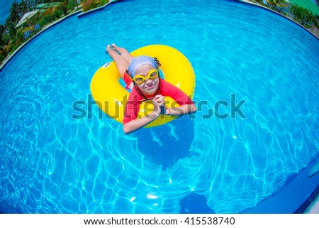 Little girl with inflatable rubber circle having fun in swimming pool