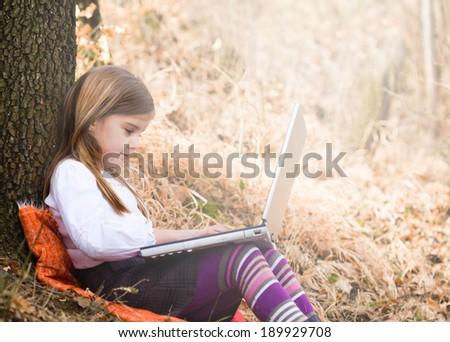 Little girl with laptop in forest - stock photo