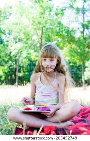 little girl with laptop in the park