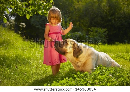 Little girl with large dog in the garden - stock photo
