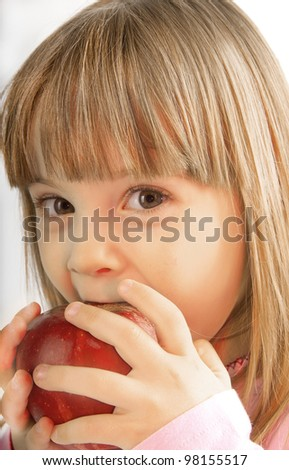 little girl with large gray eyes bite the apple