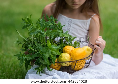Little girl with lemon and mint - stock photo